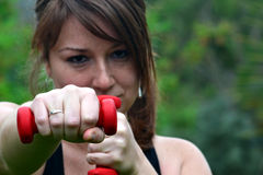 Woman with dumbbells in the park Royalty Free Stock Photos
