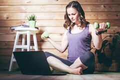 Woman with dumbbells sits in front of laptop and looks at it. Home workout concept