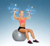 Woman with dumbbells sitting on fitness ball Stock Photography