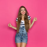 Woman In Dungarees Showing Thumbs Up Stock Image