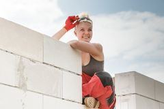 Woman in dungarees working on construction site. Happy blonde woman wearing dungarees about to do some work on construction site. Female sitting on wall made of royalty free stock photos