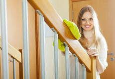 Woman dusting  railings at home Stock Image