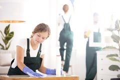 Woman dusting table. A young women in blue gloves and green overalls dusting a table royalty free stock photo