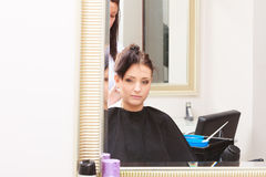 Woman dying hair in hairdressing beauty salon. By hairstylist. Stock Photo