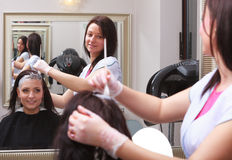 Woman dying hair in hairdressing beauty salon. By hairstylist. Royalty Free Stock Images
