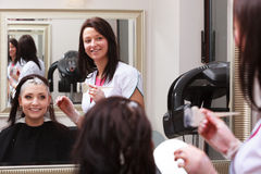 Woman dying hair in hairdressing beauty salon. By hairstylist. Royalty Free Stock Image