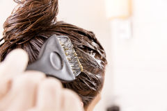 Woman dying her hair with brush in front of mirror in her own bathroom. Royalty Free Stock Photos