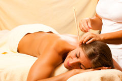 Woman with ear candles and gem massage stock photos