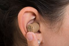 Woman Ear With Hearing Aid. Close-up Of Woman Ear Wearing Hearing Aid royalty free stock photo