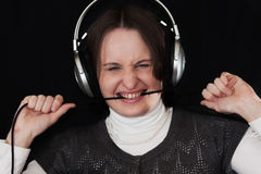 The woman in ear-phones on a black background Stock Image
