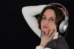 The woman in ear-phones on a black background Stock Photography