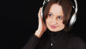 The woman in ear-phones on a black background Royalty Free Stock Photo