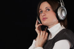 The woman in ear-phones on a black background Stock Photo