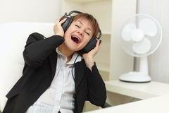 Woman with ear-phones on head sings on a workplace Royalty Free Stock Photo