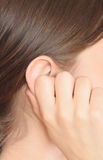 Woman ear. Young woman holding her ear Stock Photography