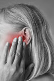 Woman with earache, ear pain closeup. Black and white photo with red spots stock photography