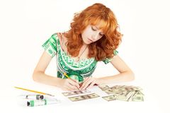 Money makes money. Woman earing a dress with a dollar print is painting bills. Forgery, money makes money royalty free stock images
