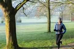 Woman On Early Morning Winter Run Through Park Keeping Fit Through Exercise. Woman On Morning Winter Run Through Park Keeping Fit Through Exercise royalty free stock photos