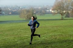 Woman On Early Morning Winter Run Through Park Keeping Fit Through Exercise. Woman On Morning Winter Run Through Park Keeping Fit Through Exercise stock photography