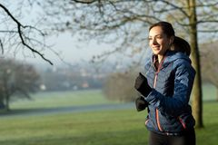 Woman On Early Morning Winter Run In Park Keeping Fit Listening To Music Through Earphones. Woman On Morning Winter Run In Park Keeping Fit Listening To Music stock photos