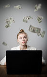 Woman earns dollars on the internet. Young slim woman using a laptop to browse the net. Woman earns money on the internet Royalty Free Stock Photo
