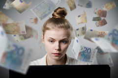 Woman earns Euro on the internet. Young slim woman using a laptop to browse the net. Woman earns money on the internet Royalty Free Stock Photos