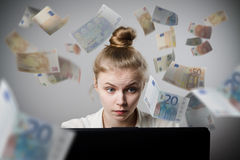 Woman earns Euro on the internet. Young slim woman using a laptop to browse the net. Woman earns money on the internet Royalty Free Stock Photo