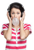 Woman with earphones and bubble gum Stock Image