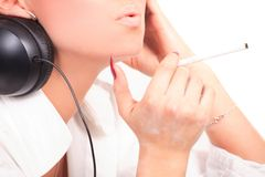Woman with earphones smoking Royalty Free Stock Image
