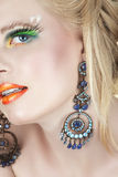 Woman with earrings and false lashes Royalty Free Stock Images