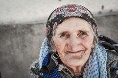 Woman with earrings in Tajikistan. Khorog, Tajikistan - circa September 2011: Older woman with headcloth and earrings smiles nicely to photocamera in Khorog Stock Photo