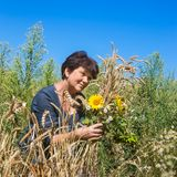 Woman with ears and sunflowers in field Royalty Free Stock Photography