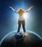 Woman on earth. Woman standing on earth with hands in praise Stock Image