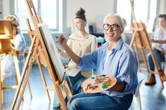 Woman by easel. Smiling mature women with palette of mixed oil paints and paintbrush sitting in front of easel royalty free stock photography