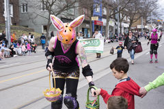 Woman in Easter costume distributes gifts to children along the Queen Street East in the Beaches Easter Parade 2017 Stock Image