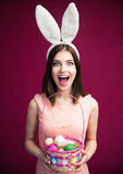 Woman with an Easter egg basket. Happy young woman with bunny ears and Easter egg basket. Looking at camera. Standing over pink background Royalty Free Stock Images