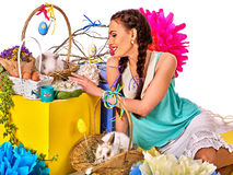Woman in easter style holding bunny and flowers. Easter girl holding bunny and eggs. Holiday style holding and group of rabbits in basket with flowers. Isolated Royalty Free Stock Photo