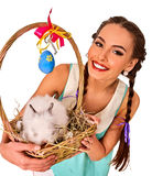Woman in easter style holding eggs and flowers. Easter girl holding bunny and decoration eggs. Holiday style holding and rabbits in basket with flowers. White Stock Photos