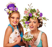 Woman in easter style holding eggs and flowers. Royalty Free Stock Images