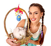 Woman in easter style holding eggs and live rabbit. Stock Image