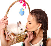 Woman in easter style holding eggs and live rabbit. Stock Photo
