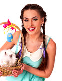 Woman in easter style holding eggs and live rabbit. Stock Images
