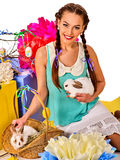 Woman in easter style holding rabbit and flowers in basket. Royalty Free Stock Photography