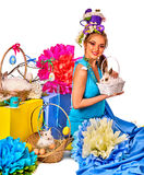 Woman in easter style holding rabbit and flowers in basket. Easter girl holding bunny and eggs. Woman with holiday hairstyle and make up holding rabbit in Stock Image