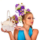 Woman in easter style holding rabbit and flowers in basket. Easter girl holding bunny and eggs. Woman with holiday hairstyle and make up holding rabbit in Royalty Free Stock Images