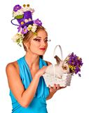 Woman in easter style holding rabbit and flowers in basket. Easter girl holding bunny and eggs. Woman with holiday hairstyle and make up holding rabbit in Stock Images