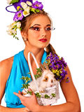 Woman in easter style holding rabbit and flowers in basket. Easter girl holding bunny and eggs. Woman with holiday hairstyle and make up holding white rabbit in Royalty Free Stock Image