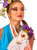 Woman in easter style holding rabbit and flowers in basket. Easter girl holding bunny and eggs. Woman with holiday spring flowers hairstyle and make up holding Stock Photo