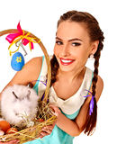 Woman in easter style keeps eggs and live rabbit. Royalty Free Stock Photography