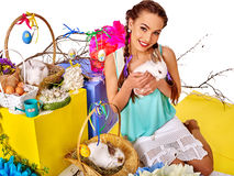 Woman in easter style keeps rabbits and flowers. Stock Photos